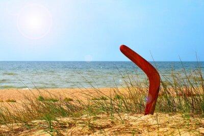 Póster Paisaje con boomerang en la playa arenosa con mucha vegetación.