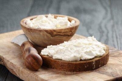 Póster pan de centeno con queso crema en la mesa de madera