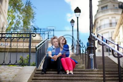 Pareja de jóvenes turistas en Montmartre sentado en las escaleras