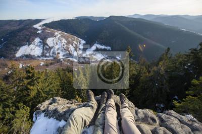 Pareja de piernas juntas en la roca en la parte superior de la montaña por el