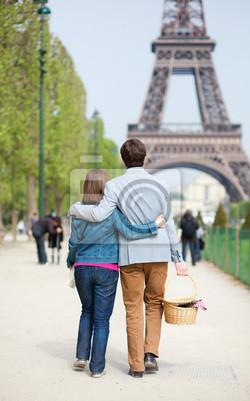 Pareja joven que va a tener un picnic en la Torre Eiffel