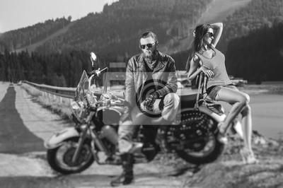 Pareja sentada en una moto. Apuesto hombre llevaba chaqueta de cuero, guantes y botas y sexy chica llevaba pantalones cortos. Día de verano en las montañas. Efecto de desenfoque de la lente de cambio