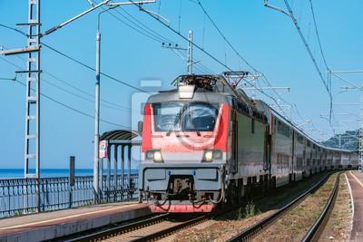 Passenger double deck train moves along the platform by the Black sea coast. Sochi. Russia.