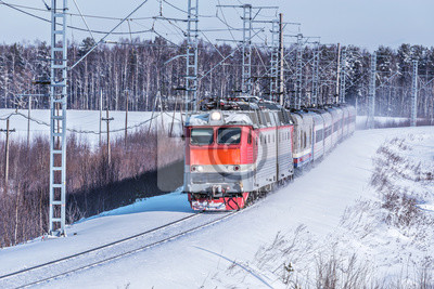 Passenger train approaches to the station at winter morning time.