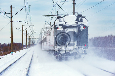 Passenger train moves at winter day time.