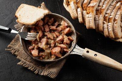 Póster Piezas de salchicha frito con cebolla