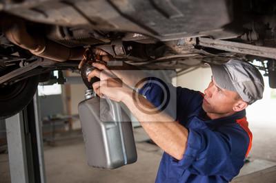 Portait de mecánico de automóviles drenaje de aceite de motor en coche levantado en r