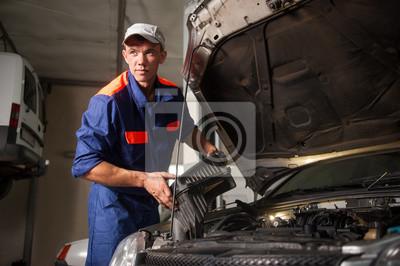 Portait de mecánico masculino que fija el motor de coche en el taller de reparación