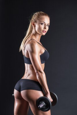 Póster Portrait of a beautiful girl athlete with a dumbbell in studio