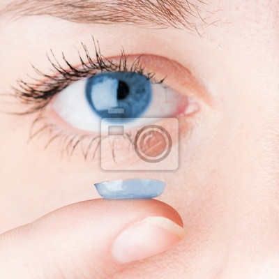 Primer plano de la inserción de una lente de contacto en ojo femenino