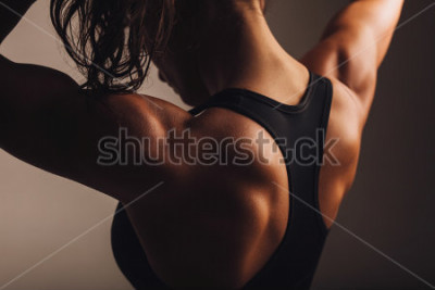 Póster Primer plano de la parte posterior del modelo fitness femenino. Mujer joven en ropa deportiva con cuerpo musculoso.
