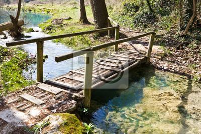 Puente de madera en el sendero junto al río Elsa, Toscana, Italia.