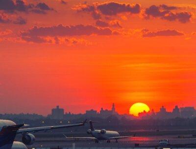 Póster Puesta de sol en el aeropuerto con aviones listos para despegar