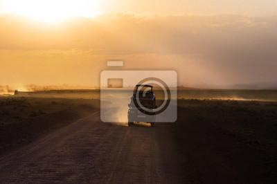Puesta de sol en la sabana africana, siluetas de coche de safari y animales, África, Kenia, Parque Nacional de Amboseli