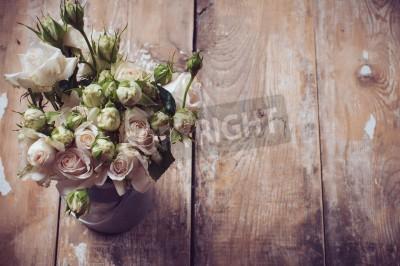 Póster Ramo de rosas en una olla de metal en el fondo de madera, estilo vintage