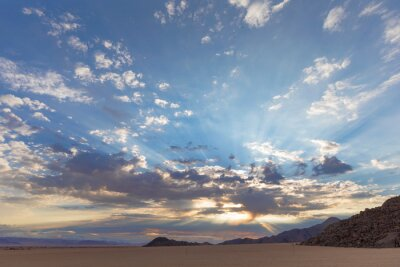 Rays from the sun behind clouds in the morning in the Namib Desert