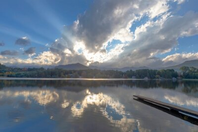 Rays of sunlight shine through the clouds above the lake