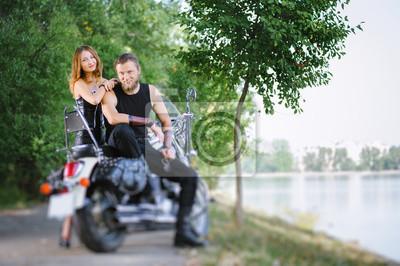 Retrato de atractivos ciclistas pareja de pie por una moto crucero cerca del lago en día de verano. Efecto de desenfoque de la lente de cambio de inclinación.