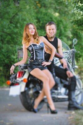 Retrato de atractivos ciclistas pareja sentado en una moto en el bosque en día de verano. Efecto de desenfoque de la lente de cambio de inclinación