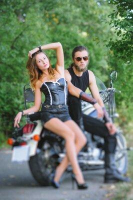 Retrato de atractivos ciclistas pareja sentado por una moto crucero en día de verano. Efecto de desenfoque de la lente de cambio de inclinación