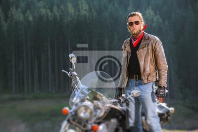 Retrato de ciclista guapo con barba de pie por su motocicleta de crucero por encargo. El hombre está usando gafas de sol de chaqueta de cuero y blue jeans con el bosque en el fondo. Efecto de desenfoq