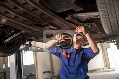 Retrato de mecánico de automóviles trabajando con herramientas bajo el coche en automob