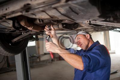 Retrato de mecánico de automóviles trabajando con herramientas bajo el coche en automoción