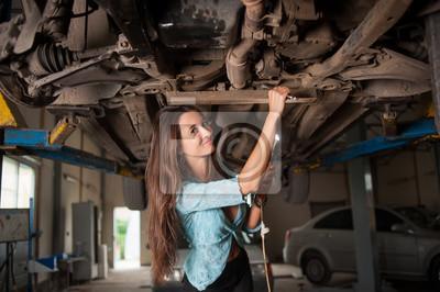 Retrato de muchacha hermosa atractiva que examina el coche levantado en el automóvil