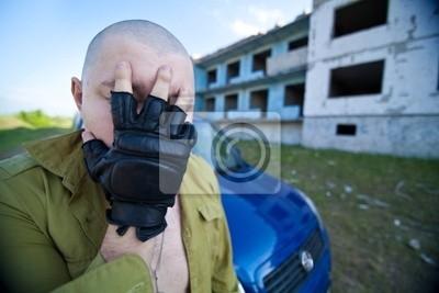 Retrato de un hombre de la cabeza rapada cerca del edificio en ruinas.