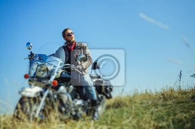 Retrato de un hombre joven con la barba que se sienta en su motocicleta del crucero. Biker lleva chaqueta de cuero y vaqueros azules. Bajo punto de vista. Efecto de desenfoque de la lente de cambio de