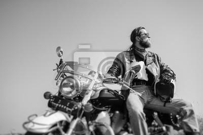 Retrato de un hombre joven con la barba que se sienta en su motocicleta del crucero. El hombre está usando chaqueta de cuero y blue jeans. Bajo punto de vista. Efecto de desenfoque de la lente de camb