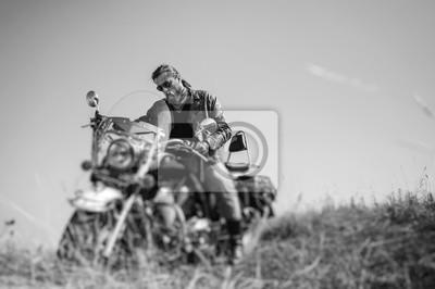 Retrato de un joven ciclista con barba sentado en su moto crucero y mirando a su bicicleta. El hombre está usando chaqueta de cuero y blue jeans. Bajo punto de vista. Efecto de desenfoque de la lente