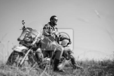 Retrato de un joven ciclista feliz con la barba sentado en su moto crucero. El hombre está usando chaqueta de cuero y blue jeans. Bajo punto de vista. Efecto de desenfoque de la lente de cambio de inc