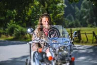 Retrato del motorista con el pelo largo y la barba en una chaqueta de cuero y las gafas de sol que se sientan en su bici al lado del camino en el bosque. Mirando a la cámara. Efecto de desenfoque de l