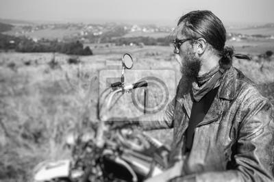 Retrato del motorista con el pelo largo y la barba en una chaqueta de cuero y las gafas de sol que se sientan en su bici en el campo herboso. Mirando en la distancia. Efecto de desenfoque de la lente