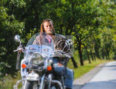 Retrato del motorista con el pelo largo y la barba en una chaqueta de cuero y las gafas de sol que se sientan en su motobike al lado de la carretera. Mirando a la cámara. Efecto de desenfoque de la le