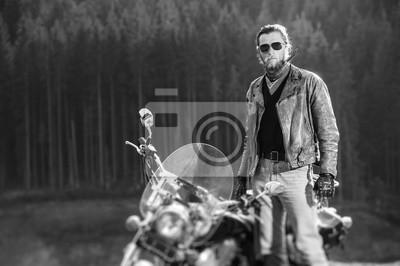 Retrato del motorista hermoso con la barba que se coloca por su motocicleta de encargo del crucero en un día asoleado con el bosque en el fondo. Efecto de desenfoque de la lente de cambio de inclinaci