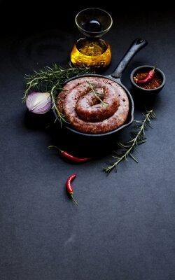 Póster Salchichas de carne cruda en una sartén de hierro fundido, enfoque selectivo
