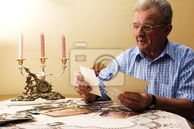 Senior hombre mirando viejas fotografías. Recordar el pasado