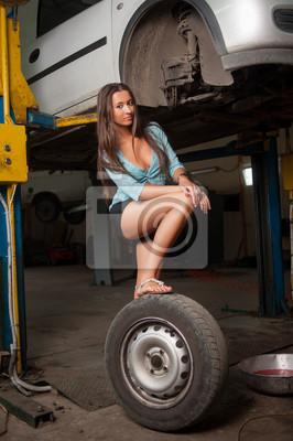Sexy hermosa chica de pie en el neumático por coche levantado en el au