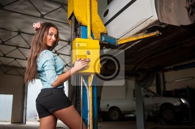 Sexy hermosa niña de pie por el coche levantado en taller de reparación de automóviles