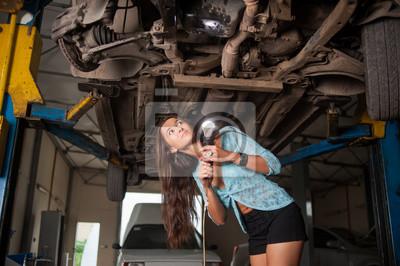Sexy hermosa niña examinando levantó el coche con la linterna en el