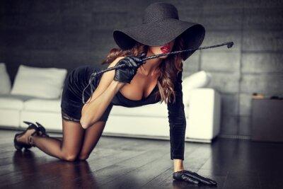 Póster Sexy mujer en sombrero y látigo arrodillado en el piso de interior