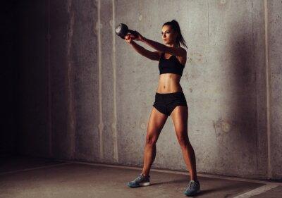 Póster Slim atractiva deportista en un entrenamiento kettlebell