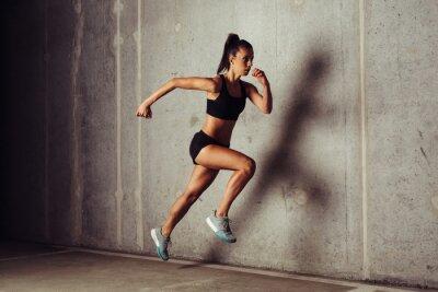 Póster Slim atractivo deportista corriendo contra un fondo de hormigón