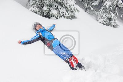 Smiling girl lying on snow drifts