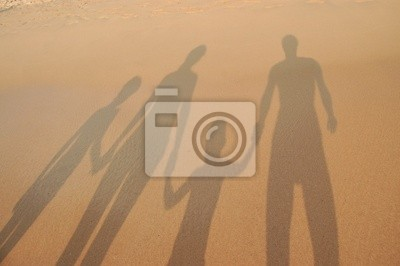 Sombras familia en la arena de playa