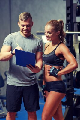 Póster Sonriente mujer joven con entrenador personal en el gimnasio