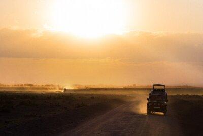Sunset in african savannah, silhouettes of safari car and animals, Africa, Kenya, Amboseli national park