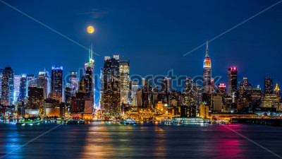 Póster Super Moon above New York skyline. The top of the Empire State Building is illuminated with the colors of the German and Argentinian flags in honor of the Soccer World Cup final.